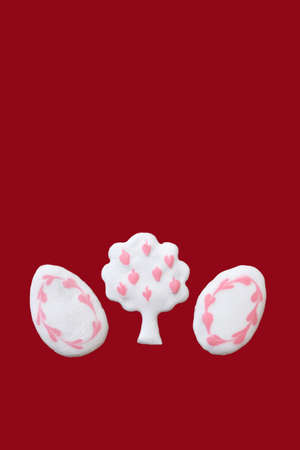 Gingerbreads in a shape of tree and eggs decorated with white and pink icing, isolated on red background. Copy space for text
