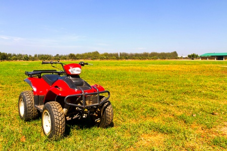 4 wheel: Red 4x4 ATV on the field Stock Photo