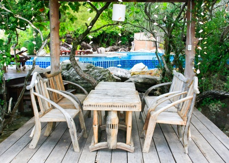 pool deck: wooden table and chairs near swimmimg pool
