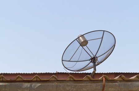 airwaves: satellite dish on the old roof with sky background