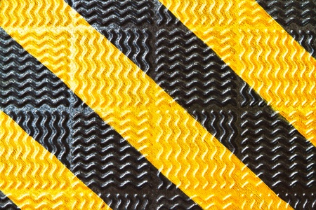 black and yellow strip on steel pavement photo