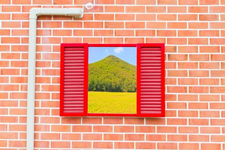 red window with mountain and green grass view on old wall photo