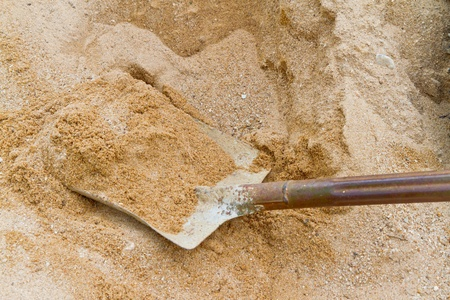 dirty steel shovel on sand photo