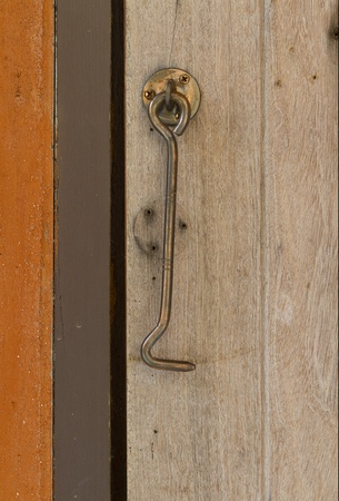 steel latch hanging on wooden wall photo