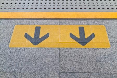 horrid: arrow line caution on ground Stock Photo