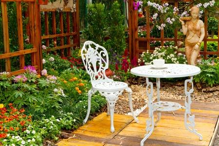 bellissimo giardino con tavolo e sedia bianca Editoriali