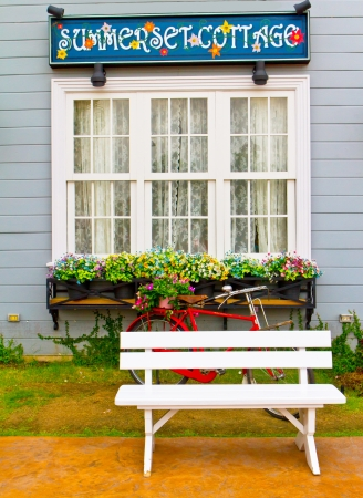 vertical garden: white wooden chair and red bicycle in garden
