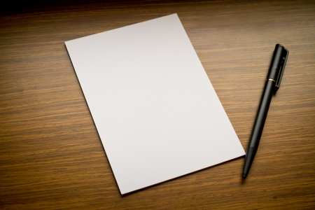 pen and white paper on wooden table photo