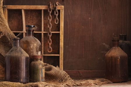 dusty: a still life composition with old dusty bottles and other objects on wood background, empty space for text