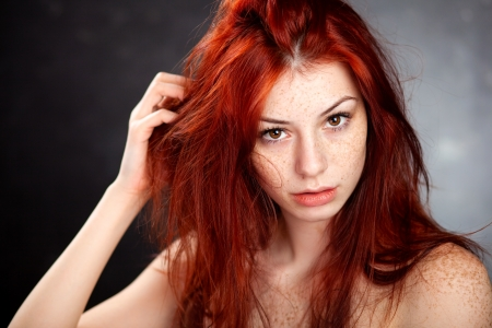 freckles: beautiful woman portrait with red hair and freckles