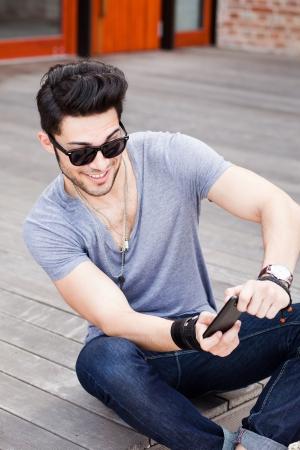 young male model: atractivo modelo masculino joven que juega juegos en un tel�fono inteligente