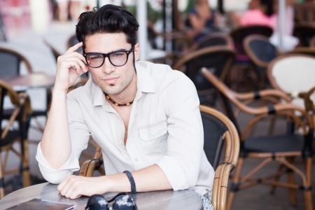 attractive man wearing glasses standing at a terrace looking cool photo