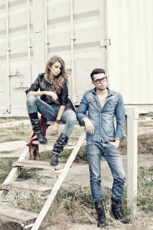 fashionable couple: pantalones vaqueros atractivos par de vestidos de moda posando dram�tico - imagen retro procesados Foto de archivo