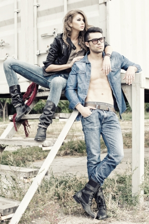 girl in jeans: stylish couple wearing jeans and boots posing dramatic - retro processed image Stock Photo
