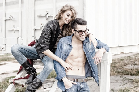 stylish couple wearing jeans and boots smiling - retro processed image photo