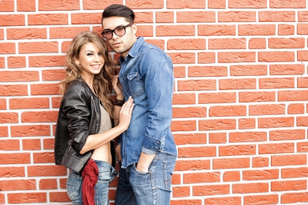 attractive fashionable couple casually leaning against brick wall