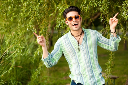 handsome man wearing sunglasses singing in the park photo