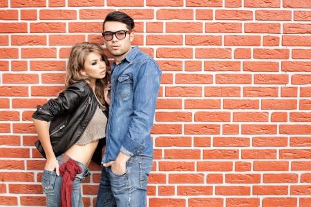 fashionable couple: pareja de moda atractivo casual apoyado contra la pared de ladrillo Foto de archivo