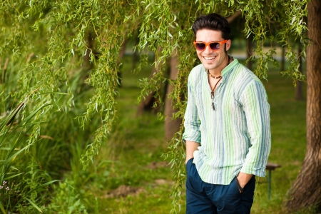 handsome man wearing sunglasses laughing in the park photo