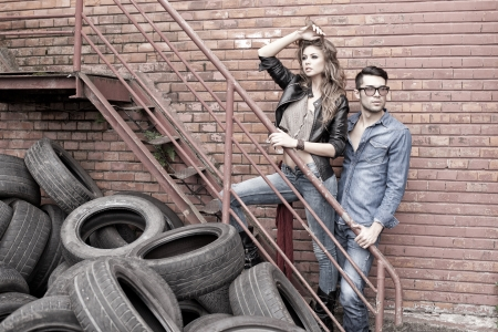denim wear: Sexy and fashionable couple wearing jeans, shoot in a grungy location - landscape orientation with copy-space Stock Photo