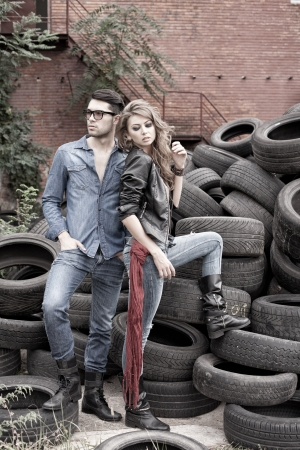 worn jeans: Sexy and fashionable couple wearing jeans, shoot in a grungy location - landscape orientation with copy-space Stock Photo