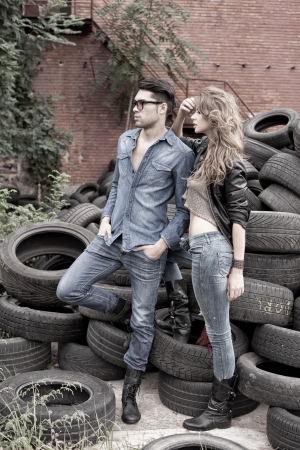 young man jeans: Sexy and fashionable couple wearing jeans, shoot in a grungy location - landscape orientation with copy-space Stock Photo