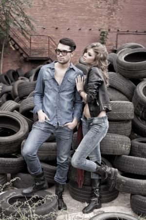 fashionable couple: Sexy par de pantalones vaqueros y vestidos de moda, grabar en un lugar sucio - orientaci�n horizontal con el copia-espacio