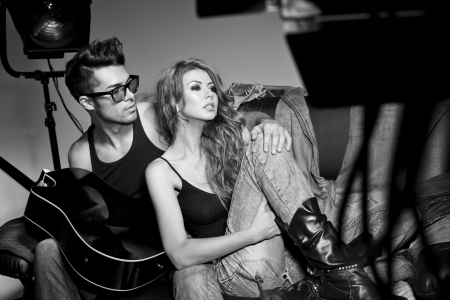 Sexy man and woman doing a fashion photo shoot in a professional studio photo