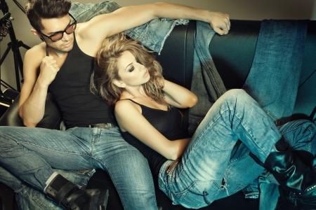 fashionable couple: Sexy hombre y una mujer vestida con pantalones vaqueros que hacen una foto de moda disparar en un estudio profesional Foto de archivo
