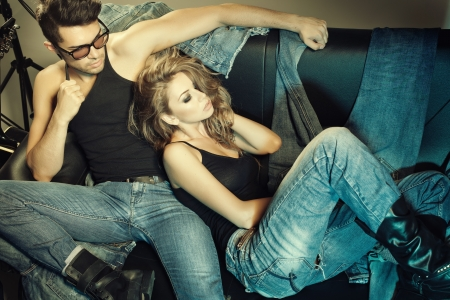 denim texture: Sexy man and woman dressed in jeans doing a fashion photo shoot in a professional studio