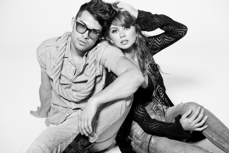 Sexy man and woman doing a fashion photo shoot in a professional studio - bw retro mood photo