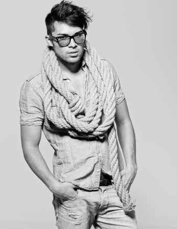Sexy man wearing glasses doing a fashion photo shoot in a professional studio photo