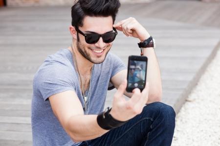 young male model: modelo masculino joven fotografiando a s� mismo con un tel�fono inteligente Foto de archivo
