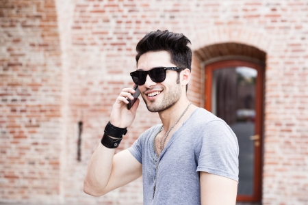 attractive young male model posing outdoors in blue shirt and sunglasses Stock Photo