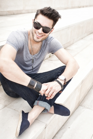 handsome male fashion model smiling, dressed casual - outdoor Фото со стока