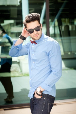 shades of grey: attractive young male model posing outdoors in blue shirt and sunglasses Stock Photo
