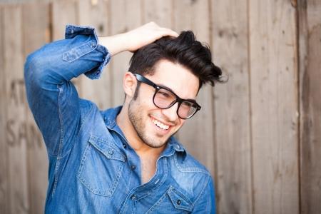 poses de modelos: hombre joven y guapo sonriendo al aire libre