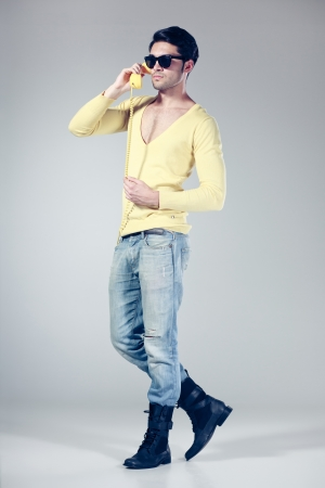 attractive man with hipster glasses talking on a yellow phone photo