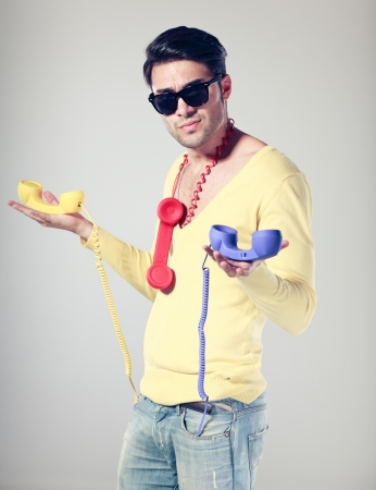 handsomen and funny guy with hipster glasses and colouful phones photo