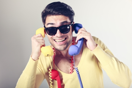 funny call center guy with hipster glasses and colouful phones Stock Photo