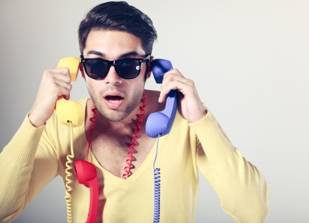 helpline: funny call center guy with hipster glasses and colouful phones Stock Photo