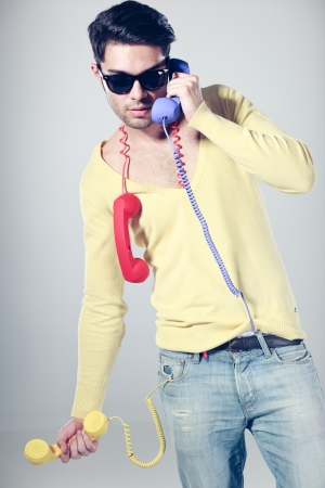 funny call center guy with hipster glasses and colouful phones photo