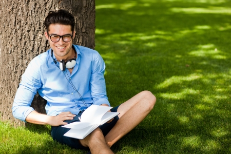 smiling man holding a book on the grass in the park photo