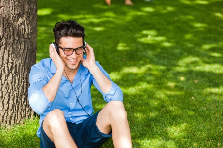 handsome man smiling and listening to music on the grass in the park photo