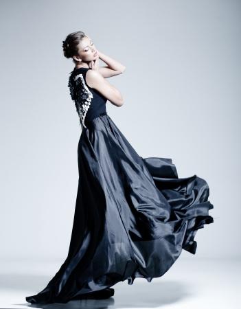 beautiful woman model dressed in an elegant dress in a fashion pose