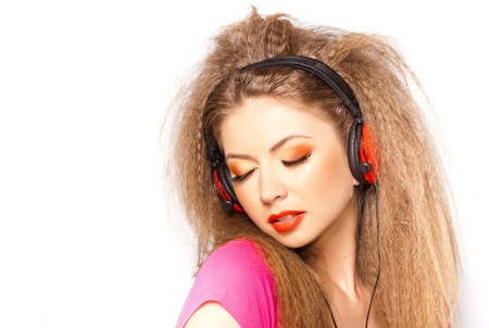sexy headphones: cute curly blonde girl listening to music on big red headphones isolated on white