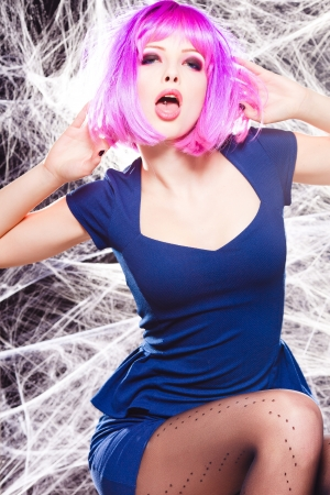 sexy woman with purple wigh and intense make-up trapped in a spider web - fashion shoot Stock Photo - 17501757