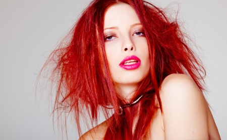 sexy red haired woman, punk attitude posing in the studio photo