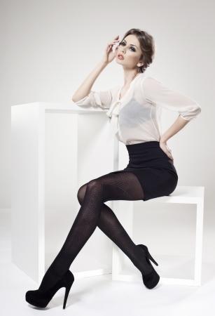 beautiful woman with long sexy legs dressed elegant posing in the studio - full body Standard-Bild