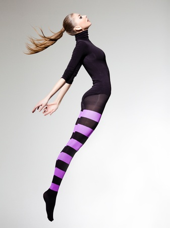 beautiful woman with perfect body jumping dressed in purple striped tights and black top Stock Photo